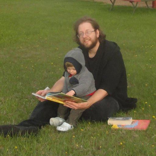 A picture of me and my son Luke, reading books in the grass on our family vacation to south dakota taken in 2012 at custer